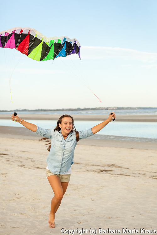 A teenage girl runs down the beach with a colorful kite in the air above her.