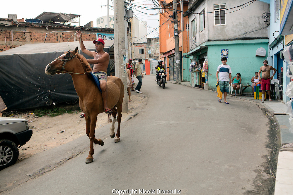Man riding horse through, Complexo do Alem&atilde;o 2013 <br />