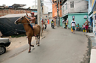 Man riding horse through, Complexo do Alemão 2013 <br />