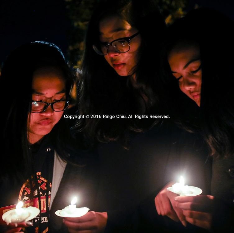 1月25日,美国洛杉矶县阿卡迪亚市,同学手拿蜡烛参加在阿卡迪亚高中举办的烛光晚会悼念两名在家中被害身亡华裔兄弟。上星期五,美国华裔聚居的洛杉矶县阿卡迪亚市发生双尸凶杀案,2名华裔高中学生为15岁的林安东尼(Anthony Lin)和他的哥哥,16岁的林威廉(William Lin),怀疑被姑父在家中用钝器杀害,其后,杀害两兄弟的姑父搭乘国泰航空离开美国,但香港国际机场被当地警察逮捕。新华社发 (赵汉荣摄)<br /> Students hold a candlelight at Arcadia High School Monday night, January 25, 2016, during a candlelight vigil for the two brothers killed by their uncle in Friday, in Arcadia, California, the United States. Two brothers, 15 and 16, were found by their parents Friday at their home near school. They appeared to have suffered blunt force trauma and were pronounced dead at he scene, official said. They were identified as Arcadia High School students William and Anthony Lin, according to a statement from the Arcadia Unified School District. Their 44-year-old uncle, identified as Deyun Shi, who is suspected of killing the boys after becoming enraged that his wife had obtained a restraining order against him and begun divorce proceedings, fled on a plane to China, but was taken into custody by Hong Kong authorities Saturday as his plane arrived at Hong Kong International Airport, officials said. Authorities are working to have him returned to California. (Xinhua/Zhao Hanrong)(Photo by Ringo Chiu/PHOTOFORMULA.com)<br /> <br /> Usage Notes: This content is intended for editorial use only. For other uses, additional clearances may be required.
