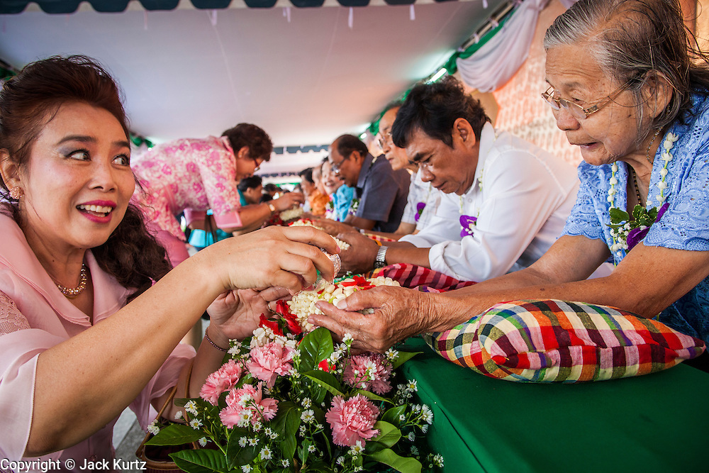 13 APRIL 2013 - BANGKOK, THAILAND:  A woman makes merit by washing the hands of an elderly woman in scented water during a Songkran observance at Bangkok City Hall. The Songkran tradition of throwing water on people started with the traditional hand washing. Songkran is the traditional Thai New Year's Festival. It is held April 13-16. Many Thais mark the holiday by going to temples and making merit by giving extra alms to monks or offering extra prayers. They also mark Songkran with joyous water fights. Songkran has been a national holiday since 1940, when Thailand moved the first day of the year to January 1.   PHOTO BY JACK KURTZ