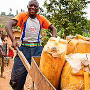 A young man hauls water in jerry cans in Kisaro, Rulindo District, Rwanda.