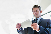 Mature businessman looking at his boarding pass in airport