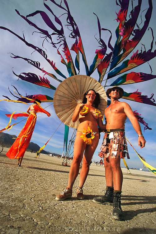 Black Rock Desert, Nevada: Burning Man is a performance art festival known for art, drugs and sex. It takes place annually in the Black Rock Desert near Gerlach, Nevada, USA..A woman wearing sunflowers holds an umbrella to guard against the desert sun. Her companion wears a skirt made of pornographic homosexual playing cards.