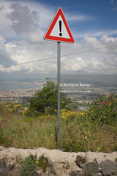Warning sign of risk on the western slope of Vesuvius with the urban sprawl of Naples in the distance.<br /> <br /> From the Introduction page of the book 'Risk Wise: Nine Everyday Adventures' by Polly Morland (Allianz, The School of Life, Profile Books, 2014).
