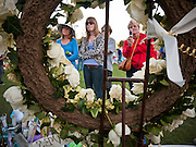 """15 JANUARY 2011 - TUCSON, AZ: People visit the memorial on the lawn in front of the University Medical Center in Tucson, AZ, Saturday, January 15. The memorial has been growing since the mass shooting last week. Six people were killed and 14 injured in the shooting spree at a """"Congress on Your Corner"""" event hosted by Congresswoman Gabrielle Giffords at a Safeway grocery store in north Tucson on January 8. Congresswoman Giffords, the intended target of the attack, was shot in the head and seriously injured in the attack. She is hospitalized at UMC. The alleged gunman, Jared Lee Loughner, was wrestled to the ground by bystanders when he stopped shooting to reload the Glock 19 semi-automatic pistol. Loughner is currently in federal custody at a medium security prison near Phoenix.  Photo by Jack Kurtz"""
