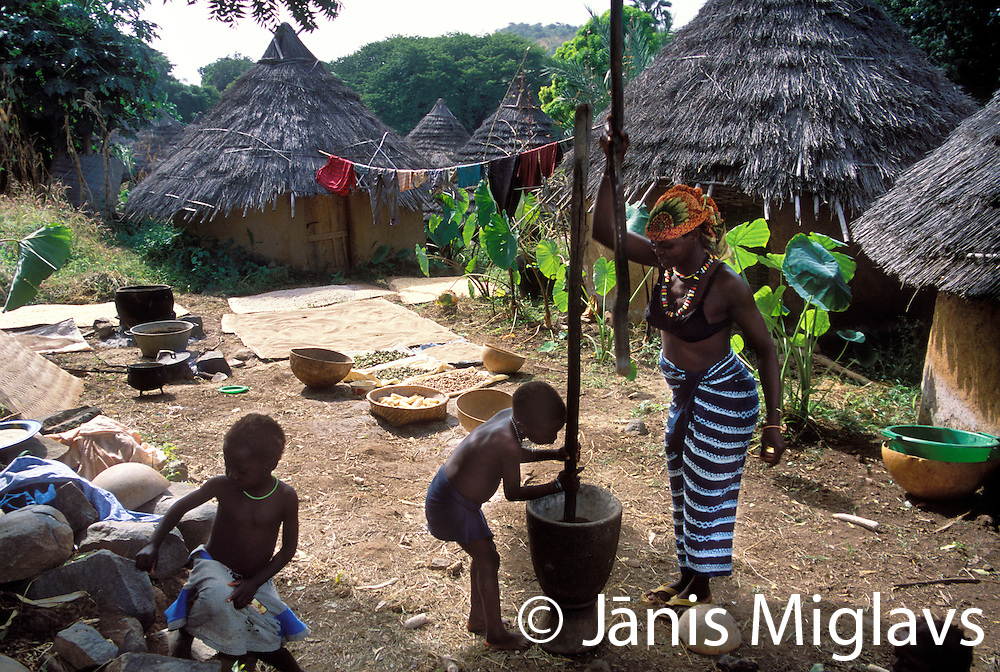 Amer Keita pounding grain with her three children. Keita is one of the two important families in village of Iwol, Senegal, West Africa.