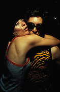 A man wearing sunglasses and woman hug in club, Le Batoter Paris, France, 1999.