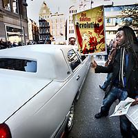 """Nederland, Amsterdam , 15 oktober 2011..sfeerimpressie van Occupy amsterdam op het Beursplein..Zaterdag zal het Beursplein in Amsterdam worden bezet door betogers van de inmiddels internationale Occupy-beweging..Wat wel centraal staat in de Occupy-beweging, zoals die ook is ontstaan in New York, is de aversie tegen het monetaire systeem en de daarbij horende hebzucht, zeggen Klifman en Lievense. """"Het is crisis na crisis, maar er is na 2,5 jaar niets veranderd"""", zegt Klifman. """"De beurskredieten, de bonussen, de hebzucht. Het gaat gewoon door."""".Op de foto: Een limousine rijdt weg uit een parkeergarage naast het Beursplein tijdens de Occupy Amsterdam..Protest in Amsterdam, the global movement Occupy at the Beursplein in front of the building of the Stock Exchange."""