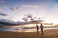 Two women walking on the beach at sunset, Kihei, Maui, Hawaii.