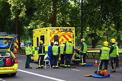London, July 7th 2017. Emergency services attend a collision between a red Toyota Prius and an ambulance on Park Lane at the intersection of Upper Grosvenor Street. There are no reported injuries, but the ambulance was carrying a patient at the time of the collision, which has closed down all but one southbound lane on Park Lane, with surrounding streets closed to traffic. PICTURED: Firefighters work on the damaged back left side of the ambulance.