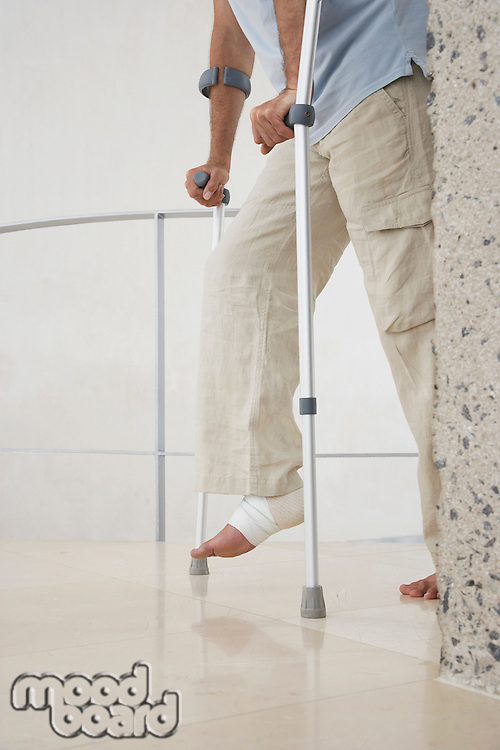 Injured man with wrapped ankle on crutches low section