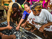 13 JULY 2016 - UBUD, BALI, INDONESIA:  People pick through the remains of a member of their family during the mass cremation in Ubud. After the remains are exhumed and burned people go through the ashes to pick out bone fragments, which are then sent to the sea. Local people in Ubud exhumed the remains of family members and burned their remains in a mass cremation ceremony Wednesday. Almost 100 people will be cremated and laid to rest in the largest mass cremation in Bali in years this week. Most of the people on Bali are Hindus. Traditional cremations in Bali are very expensive, so communities usually hold one mass cremation approximately every five years. The cremation in Ubud will conclude Saturday, with a large community ceremony.     PHOTO BY JACK KURTZ