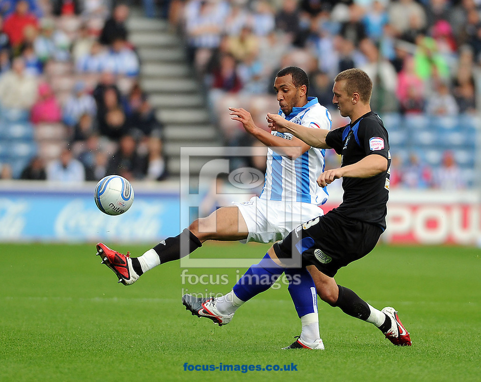 Picture by Graham Crowther/Focus Images Ltd. 07763140036.6/8/11.Calum WSoods of Huddersfield and Joe Skarz of Bury fight for the ball durng the NPower League 1 game at The Galpharm Stadium Stadium, Huddersfield.
