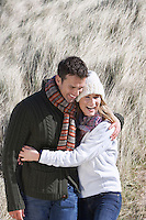 Couple embracing in long grass