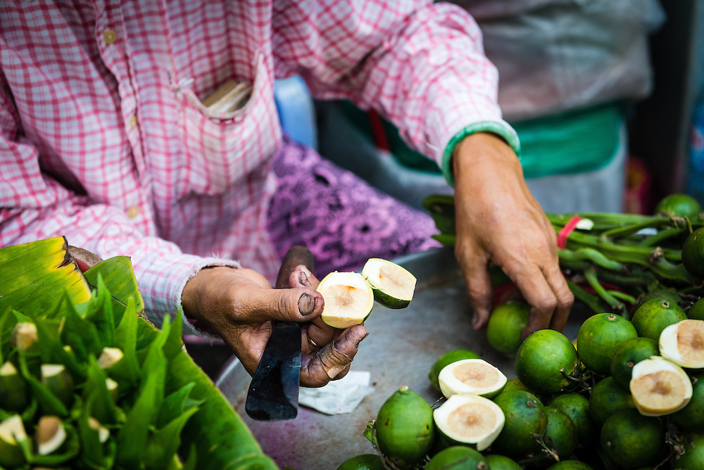Woman at street market cutting betel nut to sell