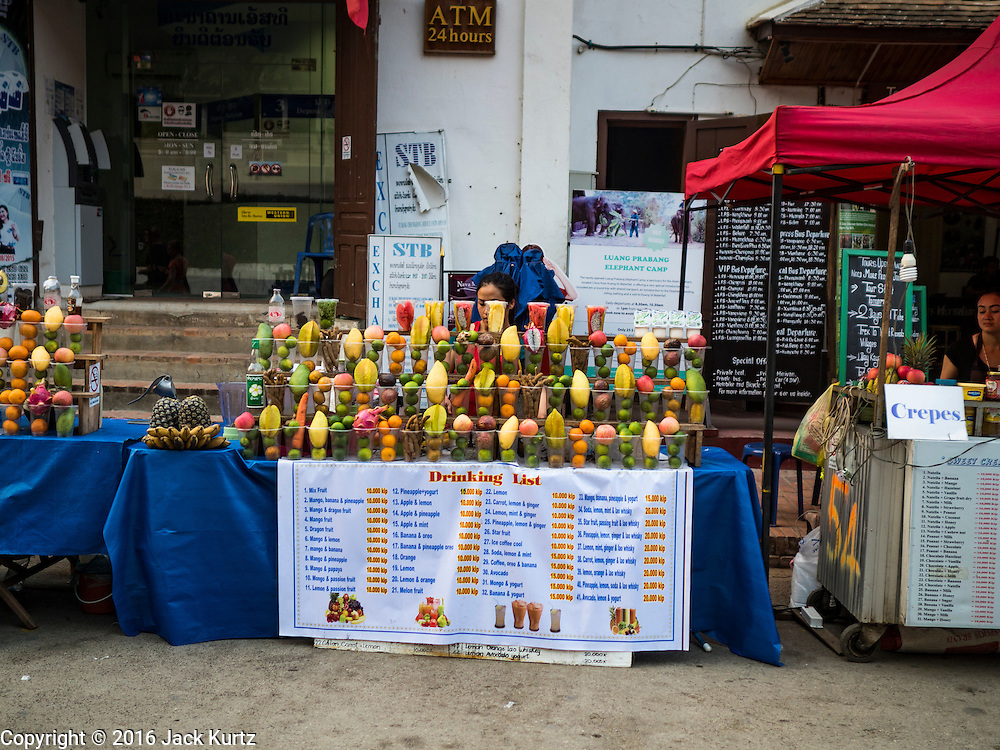 """11 MARCH 2016 - LUANG PRABANG, LAOS:  A fruit smoothie stand on the street of Luang Prabang. Luang Prabang was named a UNESCO World Heritage Site in 1995. The move saved the city's colonial architecture but the explosion of mass tourism has taken a toll on the city's soul. According to one recent study, a small plot of land that sold for $8,000 three years ago now goes for $120,000. Many longtime residents are selling their homes and moving to small developments around the city. The old homes are then converted to guesthouses, restaurants and spas. The city is famous for the morning """"tak bat,"""" or monks' morning alms rounds. Every morning hundreds of Buddhist monks come out before dawn and walk in a silent procession through the city accepting alms from residents. Now, most of the people presenting alms to the monks are tourists, since so many Lao people have moved outside of the city center. About 50,000 people are thought to live in the Luang Prabang area, the city received more than 530,000 tourists in 2014.      PHOTO BY JACK KURTZ"""