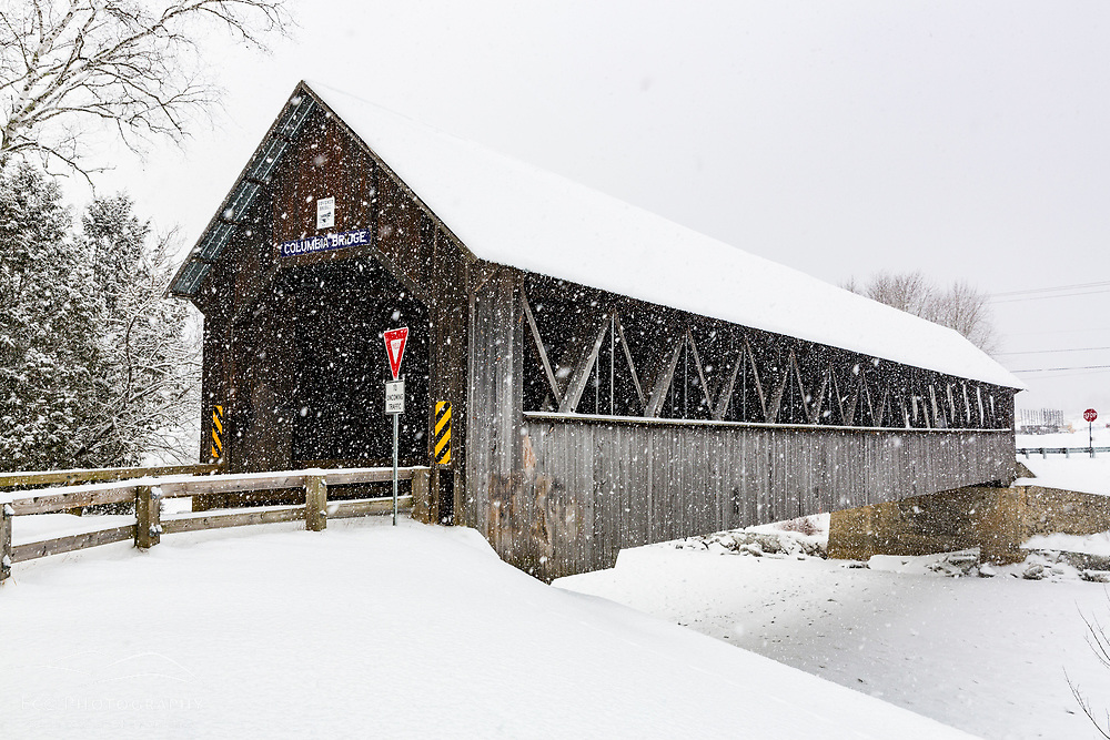 The Columbia Covered Bridge on a swnoy day in Columbia, New Hampshire.