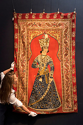 "© Licensed to London News Pictures. 20/04/2018. LONDON, UK. A technician presents ""A Qajar Rasht embroidered panel depicting a prince, Persia"", 19th century, (Est. GBP8-12k) at a preview of works in Sotheby's 20th Century Middle East, Orientalist and Islamic upcoming art sales in New Bond Street.  The works will be sold at auction in the last week of April.    Photo credit: Stephen Chung/LNP"