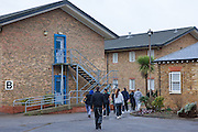 A group of prisoners are escorted throuhg the prison grounds by a prison officer. HMP Send, closed female prison. Ripley, Surrey.