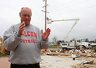 Ed Thomas, of Parkersburg, a teacher and football coach at Aplington-Parkersburg High School walks around in what was the upstairs of his house and explains where all the rooms had been as MidAmerican crews work in the background restoring power to Parkersburg, Iowa on Wednesday June 4, 2008. (Stephen Mally for the New York Times)