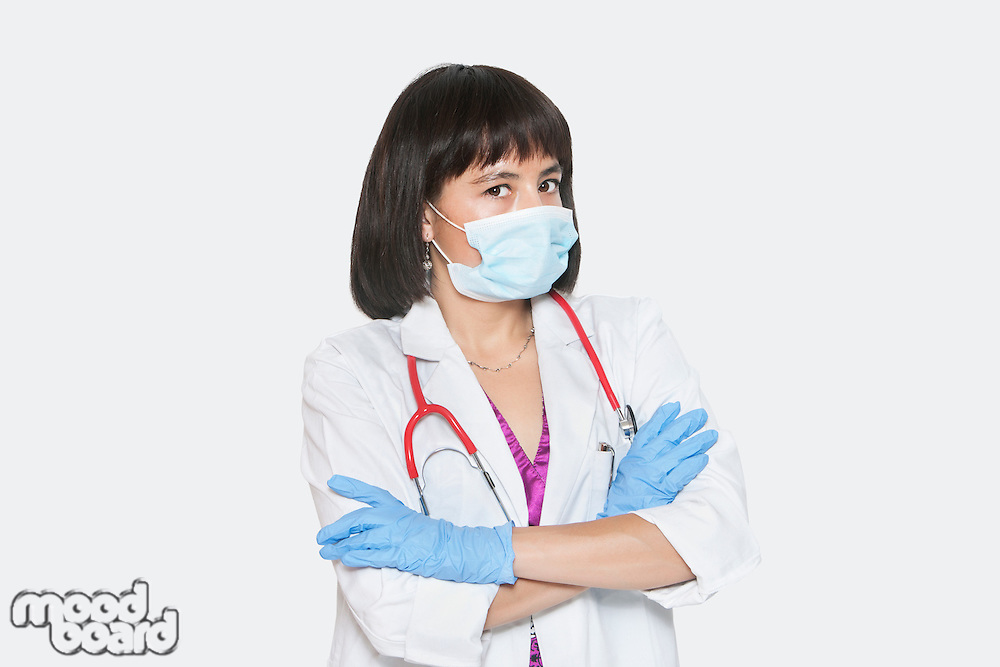 Portrait of female veterinarian standing arms crossed over gray background