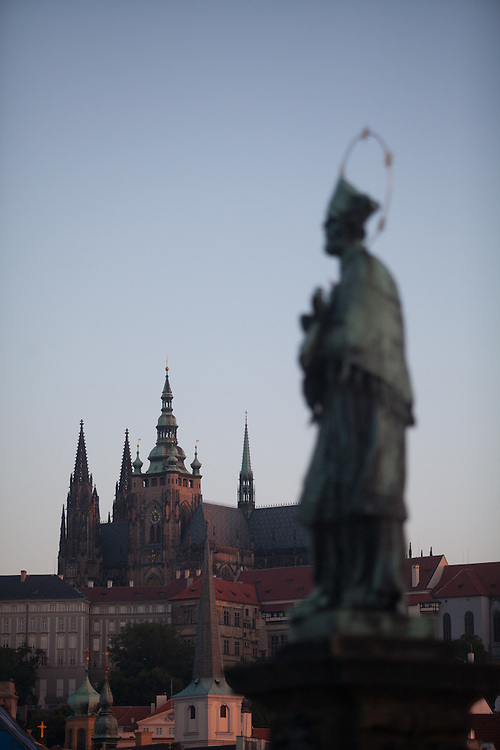 The St. John of Nepomuk Statue at Charles Bridge during early morning. St. Vitus Cathedral and Prague Castle in the back.