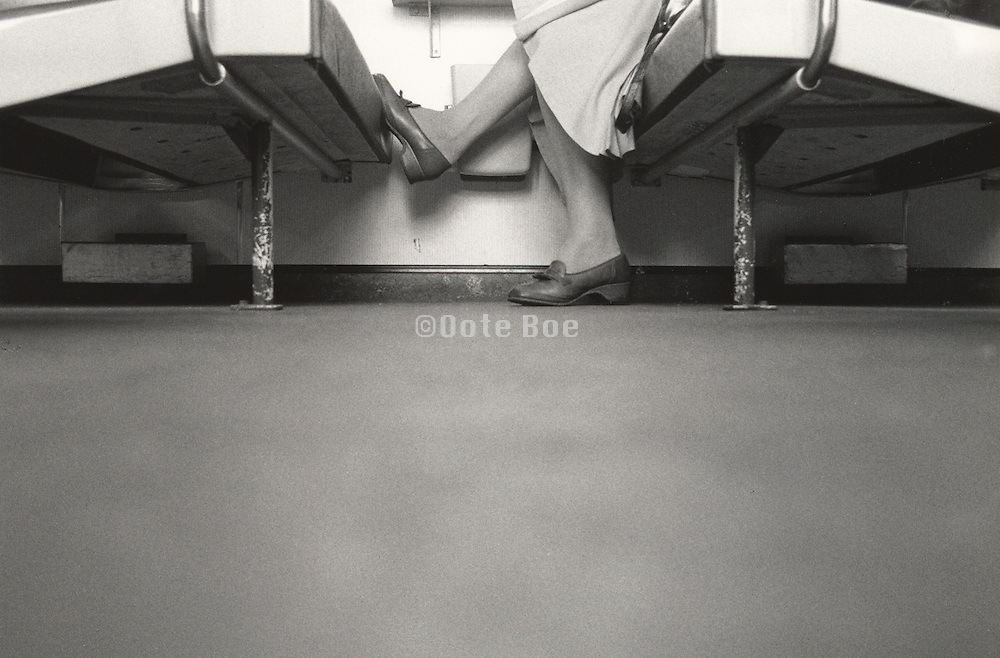 low angle view of woman seated on public transportation resting a foot