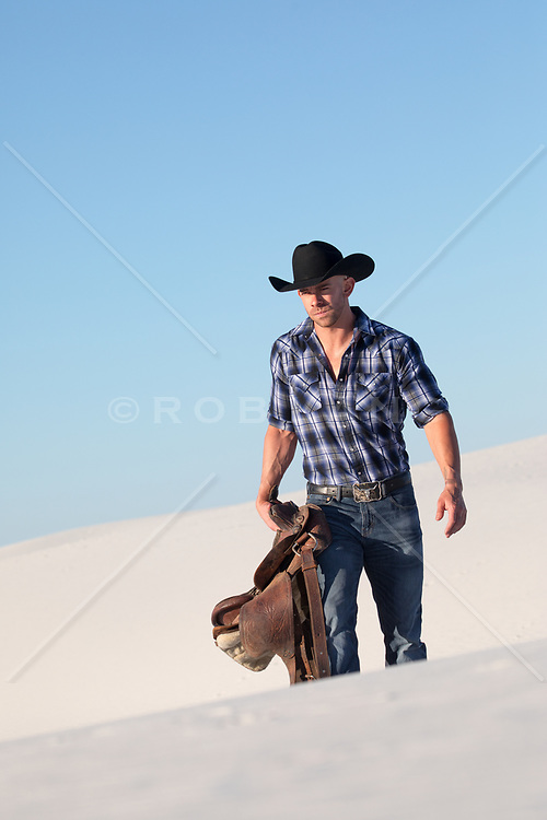 cowboy with a saddle outdoors