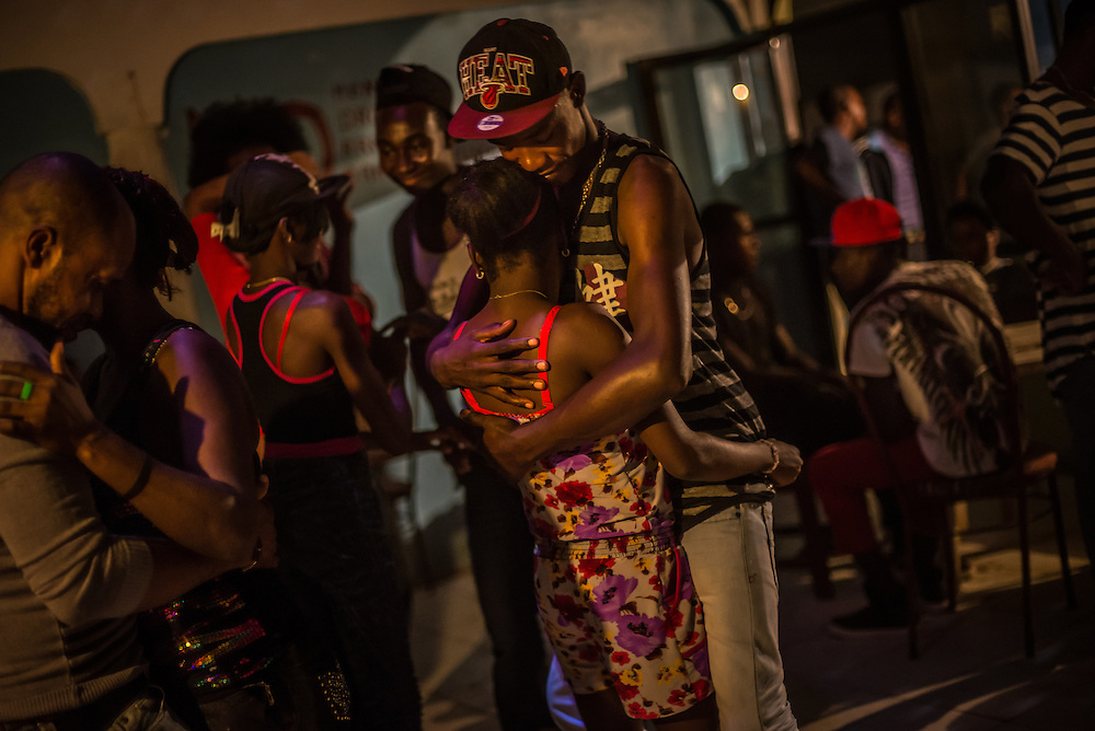 PUERTO PLATA, DOMINICAN REPUBLIC - JUNE 27, 2015:  Young Haitians and Dominicans party inside an abandoned resort where many of them live as squatters. The space that they've turned into an improvised discotheque was once the tennis pro shop.  Dozens of Haitian and poor Dominican families live as squatters inside of this abandoned resort that once attracted international tourists in Puerto Plata, on the northern coast of the Dominican Republic.  The resort became a bastion of immigrant life, especially following the 2010 earthquake in neighboring Haiti, with people having taken rooms in the hotel to live.  In recent weeks, however, it's been abandoned once again. Haitian residents were scared by the new immigration policy and many fled to other more low profile places or to back to Haiti, in fear of being deported. Their squatter community is symbolic to the changing dynamics of this town and immigration policy. It's sort of the resort that time forgot - twice abandoned and now nearly empty.  PHOTO: Meridith Kohut for The New York Times.