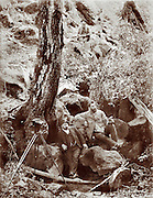 """Mungo Springs""Photographer in the American West circa 1880. A man with a gun watches over the two men in foreground.  One of the men in the foreground appears to be eating out of a can."