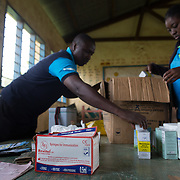 Data clerk Oscar Kai (blue shirt), at the Ngamani Primary School prepares for an outreach health clinic. Oscar will enter data about the PCV 10 vaccine, as well as pentavalent, BCG, polio, yellow fever, measles, diphtheria, tetanus and hepatitis B immunizations. All of that fresh information is then uploaded to portable hard-drives that are returned weekly to the study headquarters, where the database is updated.<br /> <br /> &quot;Because the database is digitized, it means it's far easier to keep our records fresh, even if children move and access health services in different locations,&quot; says Dr.Benjamin Tsofa, the Kenyan health ministry's chief liaison on the study. <br /> <br /> In January 2011, the Kenyan government with support from the GAVI Alliance, introduced a new vaccine, PCV-10, which targets 10 bacteria than can cause Invasive Pneumococcal Disease.The vaccine's impact is monitored through an electronic database, part of the GAVI funded PCV impact study, which maps the growing coverage of the new vaccine. Already, here in Kilifi, the incidence of the illness in children aged five has gone down by approximately two-thirds.