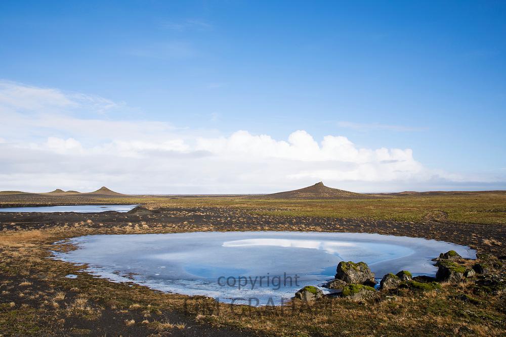 Glacial melt pond at Myrdalssandur, an outwash plain in Vatnajokull National Park, volcanic crater cones behind, South Iceland