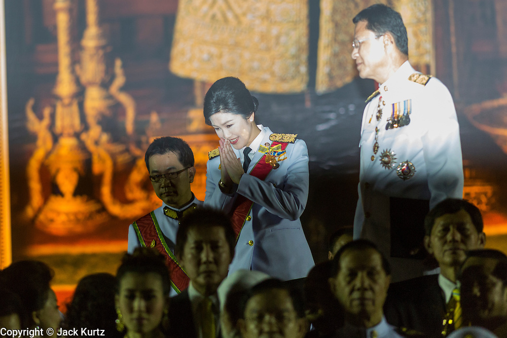 05 DECEMBER 2013 - BANGKOK, THAILAND: YINGLUCK SHINAWATRA (center) the Prime Minister of Thailand, and ANUSORN AMORNCHAT, her husband, (right) enter the celebration of the birthday of the King in Bangkok. Thais observed the 86th birthday of Bhumibol Adulyadej, the King of Thailand, their revered King on Thursday. They held candlelight services throughout the country. The political protests that have gripped Bangkok were on hold for the day, although protestors did hold their own observances of the holiday. Thousands of people attended the government celebration of the day on Sanam Luang, the large public space next to the Grand Palace in Bangkok.     PHOTO BY JACK KURTZ