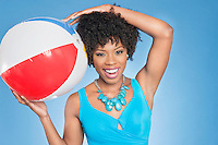 Cheerful African American woman with beach ball over colored background