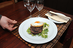© Licensed to London News Pictures. 15/02/2013. A freshly cooked horse burger is delivered to a table. A French restaurant in Kent has been selling Horse Burgers for a few months. Chez Sophie in Knockholt, near Sevenoaks, Kent,  has the burgers on its menu and is served with a fried egg and salad.  Many of the restaurants customers in the village have tried the horse burger. Photo credit : Grant Falvey/LNP