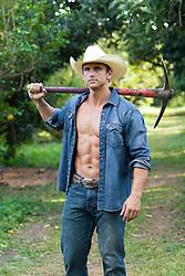 man with an open shirt carrying an axe outdoors