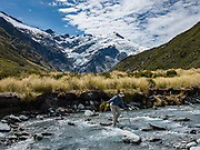 A tramper rock hops across Dart River under glacier-clad 2620m Mt Edward during a day hike from Dart Hut to Cascade Saddle, in Mount Aspiring National Park, Otago region, South Island of New Zealand.