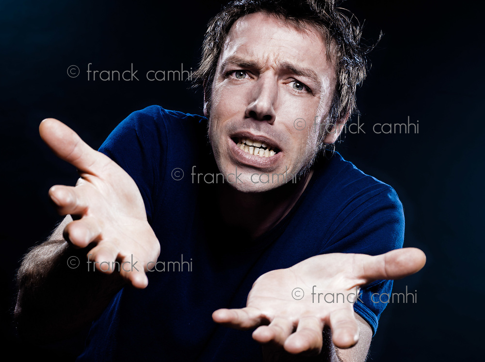 studio portrait on black background of a funny expressive caucasian man puckering helpless