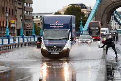 © Licensed to London News Pictures. 06/10/2019. London, UK. A man takes a photograph of a van as it drives through flooding and excess surface water on Tower Bridge this morning following heavy rain and wet weather in the capital last night. Weather forecasts predict that most of the UK will be experience heavy rain and storms during the next few days. Photo credit: Vickie Flores/LNP