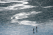 Two friends glide along the bank of a frozen Slide Lake on Saturday, enjoying a rare chance to recreate on the solid surface free of snow. As the ice expands and settles, low frequency booming sounds emanate from beneath the ice.