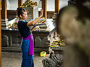 17 JULY 2016 - UBUD, BALI, INDONESIA: A woman makes an offering in the temple in the market in Ubud, Bali.      PHOTO BY JACK KURTZ