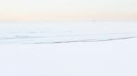 Frostrøyk og bølger som ruller mot stranden på Borestranden på Jæren. Klepp kommune, Rogaland. Feistein fyr sees i bakgrunnen.