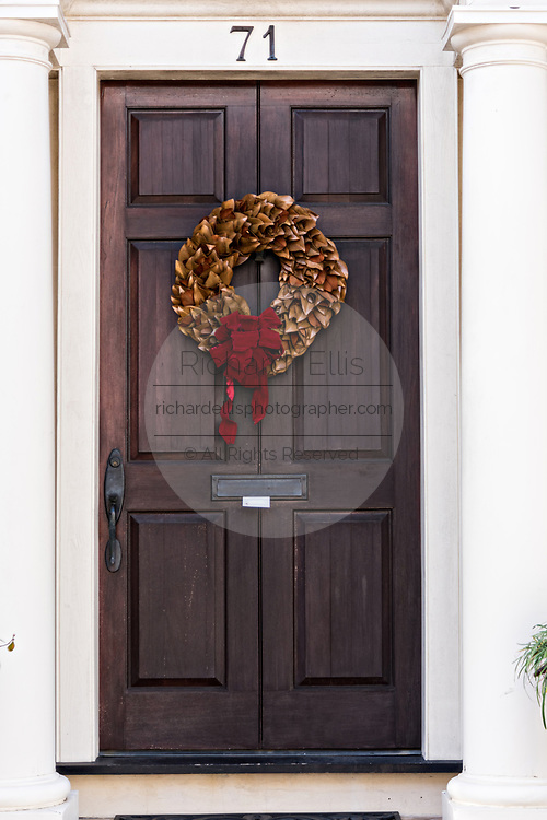 A Magnolia leaf Christmas wreath hangs from a wooden door on a historic home along King Street in Charleston, SC.