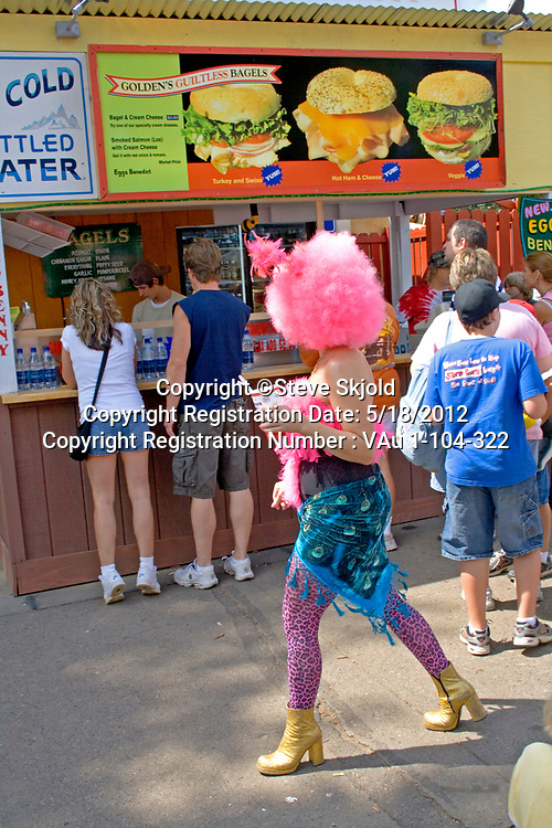 Artistically dressed woman wearing a pink wig walking by a bagel sandwich shop. Minnesota State Fair St Paul Minnesota MN USA