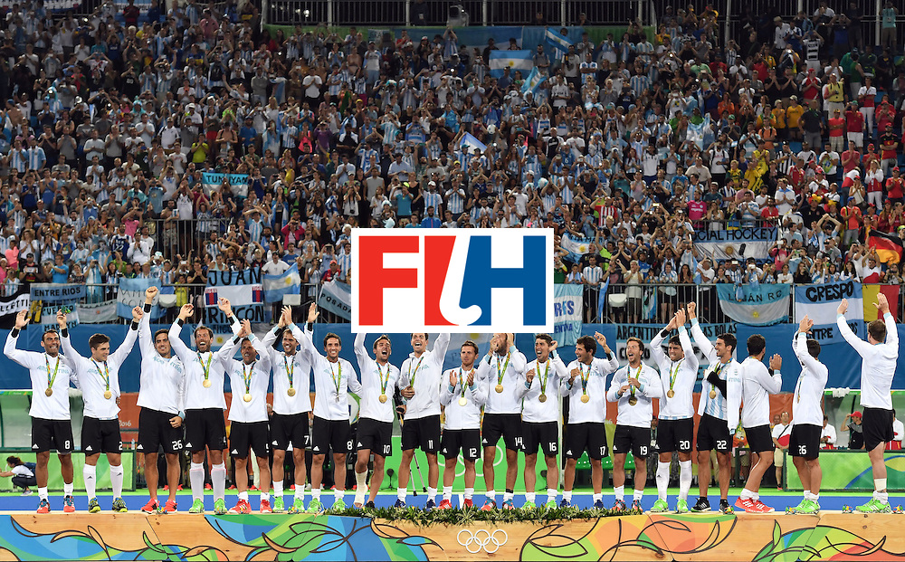 Argentina's players pose with their gold medals on the podium during the men's field hockey medals ceremony of the Rio 2016 Olympics Games at the Olympic Hockey Centre in Rio de Janeiro on August 18, 2016. / AFP / Pascal GUYOT        (Photo credit should read PASCAL GUYOT/AFP/Getty Images)