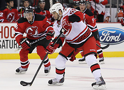 Oct 10; Newark, NJ, USA; Carolina Hurricanes right wing Chad LaRose (59) takes a shot while being defended by New Jersey Devils right wing Petr Sykora (15) during the first period at the Prudential Center.
