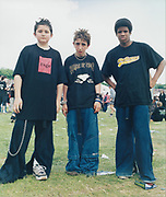 Three young punk rockers standing slouched forward posing.