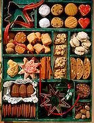 An assortment of cookies is arranged in a partitioned green box with ornaments and ribbon.