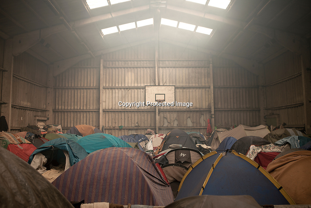 Illegal immigrants from Africa, Asia and the Middle East living in an abandoned basketball gym in Calais, France. They hope to reach UK illegaly by jump on a truck and get on the ferry to Dover.